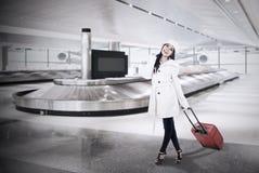 美丽的妇女在机场收集皮箱 免版税库存照片