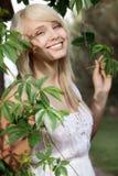 美丽的妇女在植物中 免版税库存图片