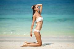 年轻俏丽的妇女在沙子放松在海滩 免版税图库摄影