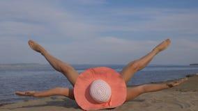 美丽的妇女在海滩说谎并且做着准备腿 股票录像