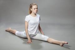 年轻美丽的妇女在灰色背景做锻炼 免版税图库摄影
