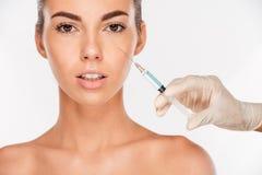 美丽的妇女在眼睛区域得到秀丽射入与注射器 免版税库存照片