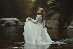 美丽的妇女在神秘的水域中 免版税图库摄影