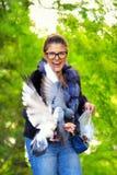 美丽的妇女在秋天公园喂养鸽子并且笑 免版税库存照片