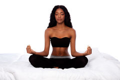 美丽的妇女在莲花瑜伽姿势坐床 免版税库存照片