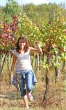美丽的妇女在葡萄园里在秋天用葡萄 免版税库存图片