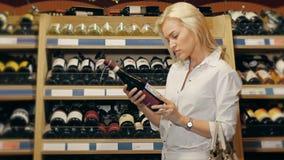 年轻美丽的妇女在超级市场选择酒 免版税库存图片