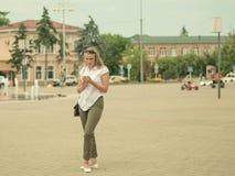 年轻美丽的妇女在镇中心通过一个电子设备沟通 免版税图库摄影