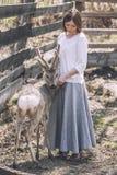 年轻美丽的妇女在阳光下的拥抱动物狍 免版税库存照片