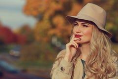 美丽的妇女在黄色槭树庭院背景认为 关闭时兴的女孩, copyspace 免版税库存图片