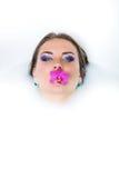 美丽的妇女在嘴保留百合 库存图片