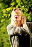 美丽的妇女在晴朗的森林里,盖她的面孔用头发, 免版税库存照片