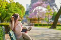 美丽的妇女在巴黎,读户外 免版税图库摄影