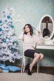 美丽的妇女坐一把椅子在新年内部 免版税库存照片