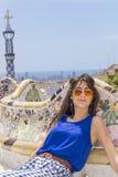 美丽的妇女坐一条长凳在公园Guel,巴塞罗那,西班牙 免版税库存图片