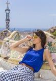 美丽的妇女坐一条长凳在公园Guel,巴塞罗那,西班牙 库存图片