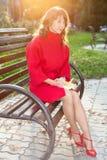 年轻美丽的妇女坐一条长凳在秋天公园 免版税图库摄影