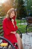 年轻美丽的妇女坐一条长凳在秋天公园 免版税库存照片