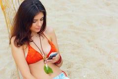 美丽的妇女坐与她的智能手机的海滩 免版税库存图片