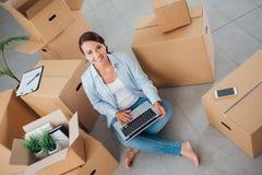 美丽的妇女坐与膝上型计算机的地板 免版税库存照片