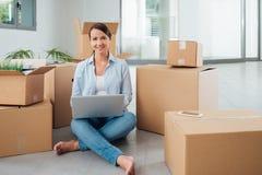 美丽的妇女坐与膝上型计算机的地板 免版税库存图片