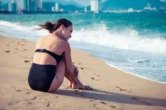 美丽的妇女坐在享受暑假的黑泳装的海滩看海 库存图片