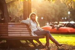 美丽的妇女坐在日落的一条长凳 库存图片