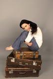 美丽的妇女坐在灰色背景的一个手提箱 工作室 免版税库存照片