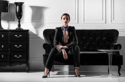 年轻美丽的妇女坐在minimalistic inteior的沙发 免版税库存照片