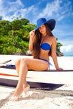 美丽的妇女坐地方小船在海附近 免版税库存图片