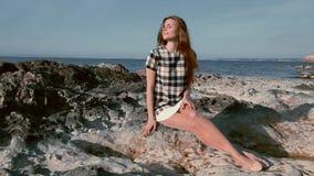 美丽的妇女坐岩石沿海地带 影视素材