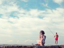 年轻美丽的妇女坐码头 库存照片