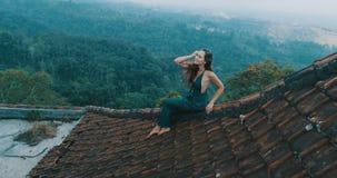 美丽的妇女坐红色房子屋顶 免版税库存照片