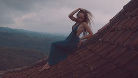 美丽的妇女坐红色房子屋顶 免版税库存图片