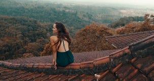 美丽的妇女坐红色房子屋顶 库存图片