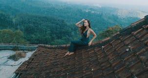 美丽的妇女坐红色房子屋顶 图库摄影