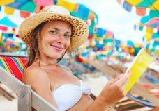 美丽的妇女坐读书的海滩 免版税库存图片