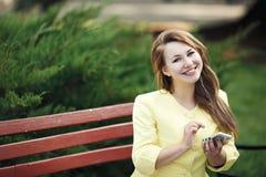 年轻美丽的妇女坐长凳以绿色 免版税库存照片