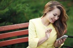 年轻美丽的妇女坐长凳以绿色 库存照片