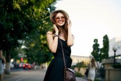 年轻美丽的妇女太阳镜的和一个帽子的在户外夏天,微笑 免版税库存照片