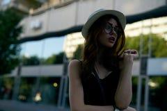 年轻美丽的妇女太阳镜的和一个白色帽子的在城市 免版税库存照片