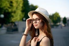 年轻美丽的妇女太阳镜的和在街道上的一个白色帽子的在城市 免版税库存图片