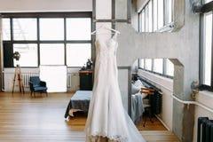 美丽的妇女婚礼礼服在挂衣架称在墙壁上的大大厅里 免版税库存照片