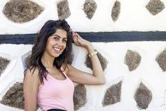 年轻美丽的妇女对老石墙,室外射击 免版税图库摄影