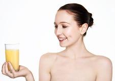 美丽的妇女对负玻璃用橙汁 免版税库存照片