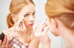 年轻美丽的妇女应用构成镜子眼影膏前面  免版税库存照片
