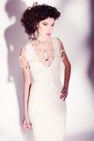 美丽的妇女式样摆在典雅的珍珠礼服在演播室 免版税图库摄影