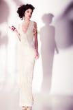美丽的妇女式样摆在典雅的珍珠礼服在演播室 库存图片
