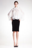 美丽的妇女式样摆在典雅的白色女衬衫和黑礼服 库存图片