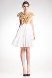 美丽的妇女式样摆在典雅的金子和白色礼服 免版税库存图片